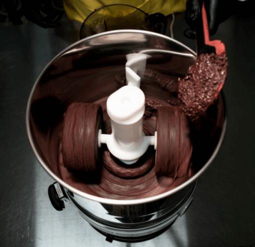 Imagem mostra equipamento específico - parecido com uma panela metálica - utilizado na fabricação de chocolate bean-to-bar, com a massa de chocolate sendo enrolada dentro do utensílio e uma concha vermelha trazendo mais nibs. Fonte: http://www.beantobarbrasil.com.br