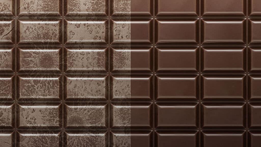 imagem mostra barra de chocolate com aspecto normal na porção do lado direito e aspecto esbranquiçado no lado esquerdo - caracterizando o fenômeno fat bloom. Fonte: https://www.desidrat.com.br/blog/tag/fat-bloom/